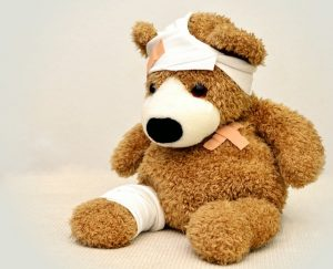 a brown stuffed bear with bandages