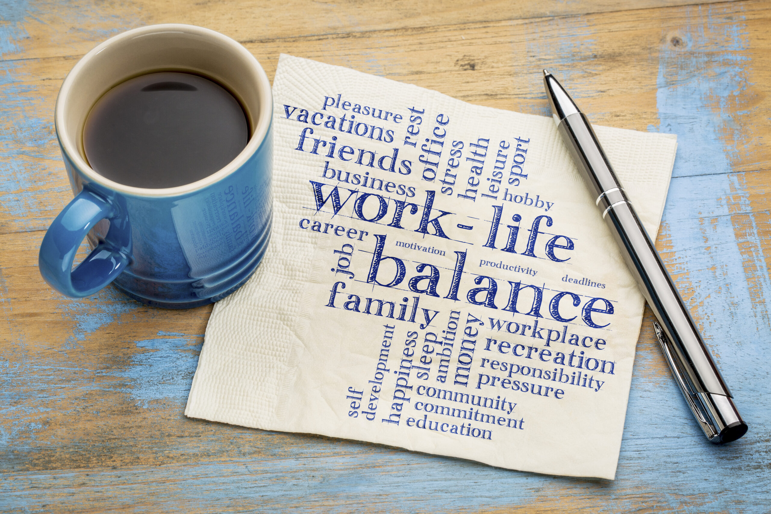 a cup beside a paper with work & life balance written on it